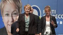 Parti Quebecois Leader Pauline Marois, left, and her press attache Marie Barrette walk from her campaign bus, Thursday August 9,2012. (Clement Allard/The Canadian Press)