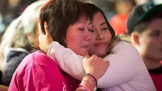 Amanda Todd's mother Carol Todd, left, is comforted by singer Elise Estrada as they watch her music video for the song