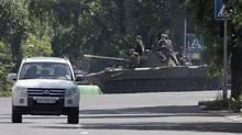 Pro-Russian fighters ride a airborne self-propelled artillery gun Nona in downtown Donetsk, eastern Ukraine Thursday, July 24. (Dmitry Lovetsky/AP)