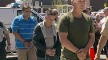 Former Montreal Maine and Atlantic Railway Ltd. employees Thomas Harding, right, Jean Demaitre, centre, and Richard Labrie are escorted by police to appear in court in Lac-Megantic, Que., on Tuesday, May 13, 2014. The Crown announced late Monday that Montreal Maine and Atlantic Railway Ltd. and three employees of the insolvent railway will each face 47 counts of criminal negligence causing death. THE CANADIAN PRESS/Ryan Remiorz (Ryan Remiorz/THE CANADIAN PRESS)