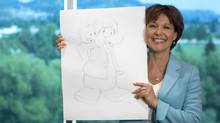 B.C. Premier Christie Clark holds up a sketch of herself as a penguin, drawn during a campaign stop at Club Penguin, a Disney-owned video-game company, in Kelowna on July 9, 2013. (JOHN LEHMANN/THE GLOBE AND MAIL)