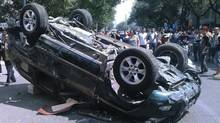 In this Sept. 15, 2012 file photo, residents look at an overturned Toyota car during an anti-Japan protest in Xi'an in northwest China's Shaanxi province. (AP)