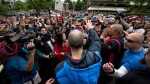 Former Vancouver Canucks' enforcer Gino Odjick, centre, waves to hundreds of fans that gathered to support him outside Vancouver General Hospital in Vancouver, B.C., on Sunday June 29, 2014. (DARRYL DYCK/THE CANADIAN PRESS)