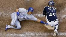 Milwaukee Brewers catcher Jonathan Lucroy can't handle the throw as Toronto Blue Jays' Munenori Kawasaki slides safely home during the sixth inning of a baseball game Wednesday, Aug. 20, 2014, in Milwaukee. (Associated Press)