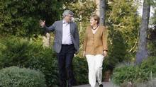 Stephen Harper walks with Germany's Chancellor Angela Merkel at Harrington Lake, the Prime Minister's official country retreat, on Wednesday. (CHRIS WATTIE/Reuters)