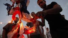 Libyan followers of Ansar al-Shariah Brigades burn the U.S. flag during a protest in front of the Tibesti Hotel, in Benghazi, Libya, Friday, Sept. 14, 2012. (Mohammad Hannon/AP)
