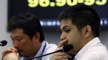 Foreign exchange brokers sit in front of an electronic board displaying the Japanese yen's exchange rate against the euro at a trading room in Tokyo on Friday. (YURIKO NAKAO/REUTERS)