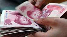 A shop assistant checks hundred yuan bank notes at a shop in Xiangfan, central China's Hubei province, August 19, 2006. (Stringer/REUTERS)