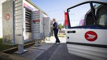 A Canada Post letter carrier puts mail in a new Canada Post super box in Calgary, Alberta, October 20, 2014. (Todd Korol For The Globe and Mail)