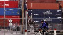 A cyclist rides past containers in the Port of Vancouver in this file photo. (Chuck Stoody/CP)