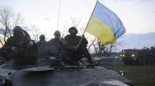 In this photo taken on Monday, April 14, 2014, Ukrainian soldiers sit on top of military vehicles with a Ukrainian national flag in a field about 70 kilometers (44 miles) from the eastern Ukrainian town of Slovyansk, where the Ukrainian regional administration building was seized by pro-Russian activists. (Maxim Dondyuk/AP)
