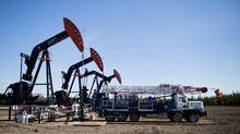 A service rig sits ready next to pumpjacks on a well pad outside of Fox Creek, Alta., in this file photo. (Amber Bracken For The Globe and Mail)