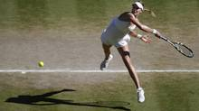 Eugenie Bouchard of Canada leaps as she plays a rerun to Simona Halep of Romania during their women's singles semi-final match at the All England Lawn Tennis Championships in Wimbledon, London, Thursday, July 3, 2014. (Associated Press)