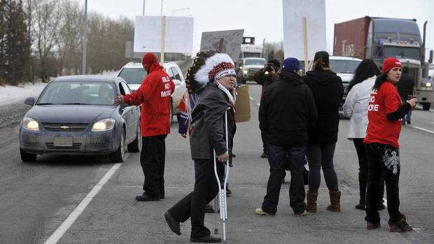 Chief Calvin Bruneau, middle, joins demonstrators as they stop traffic on the QEII highway south of Edmonton.