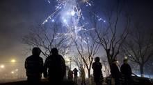 People watch fireworks on the Chinese Lunar New Year's Eve in Beijing on Jan. 23, 2012. (Alexander F. Yuan/Alexander F. Yuan/Associated Press)