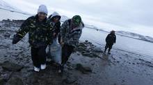 Schoolchildren who ran to the beach to meet the hunters returning from a seal hunt, are happy to help after being instructed by the elder behind how to carry the dead animal at Cape Dorset, Nunavut, on Nov. 10, 2010. (Peter Power/The Globe and Mail)