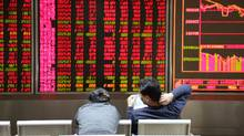 Investors observe stock market at an exchange hall on January 6, 2016 in Beijing, China. (ChinaFotoPress/Getty Images)