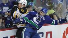 Boston Bruins Andrew Ference is checked by Vancouver Canucks Maxim Lapierre in the first period of game five of the Stanley Cup final playoff hockey action in Vancouver June 10, 2011. (JOHN LEHMANN/JOHN LEHMANN/THE GLOBE AND MAIL)