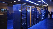 People peer into a server room during the grand opening of Hewlett-Packard's executive briefing centre in Palo Alto, Calif., Jan. 16, 2013. (STEPHEN LAM/REUTERS)