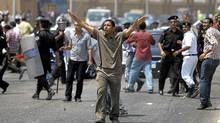 An Egyptian anti-Mubarak protester reacts during clashes with pro-Mubarak protesters outside the police academy in Cairo, Aug. 15, 2011. (Khalil Hamra/AP)
