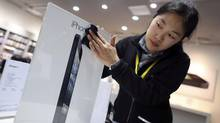 An employee cleans an advertisement at an Apple dealership in Wuhan, Hubei province in a file photo. China's state-run media outlets have been running articles and editorials criticizing the tech company. (DARLEY SHEN/REUTERS)