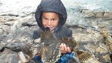 Hans Onalik, 5, shows off a kanajuk caught from shore in Pond Inlet. Kanajuk are called shorthorn sculpin in English. (Mike W. Bryant)