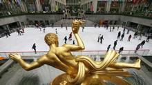 People skate on the ice beneath the gilded statue of Prometheus in Rockefeller Center in New York, October 12, 2009. (MIKE SEGAR/REUTERS)