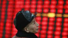 An investor watches an electronic board showing stock information at a brokerage house in Huaibei, China on Dec. 14, 2012. (REUTERS)