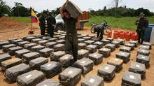 Counter narcotics police officers inspect packages containing cocaine seized in Necocli, in northwestern Colombia, Saturday, May 30, 2009. (William Fernando Martinez)