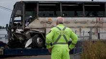A Commercial Vehicle Safety and Enforcement officer watches as a tour bus that rolled over and crashed on the Coquihalla Highway south of Merritt, B.C., Thursday, is moved during an investigation at a towing company lot in Kelowna on Friday August 29, 2014. (DARRYL DYCK/THE CANADIAN PRESS)