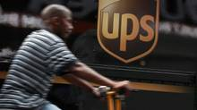 A bicycle delivery man rides past a UPS truck in New York's Times Square, July 23, 2012. (BRENDAN MCDERMID/REUTERS)