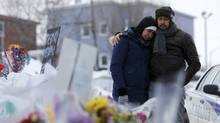 Azzedine Najd, right, and his wife Fadwa Achmaoui look at a memorial near the site of a fatal shooting at the Centre culturel islamique de Québec on Tuesday. (Mathieu Belanger/Reuters)