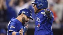 Toronto Blue Jays' Jose Bautista, left, and Edwin Encarnacion celebrate after scoring on a three-run double by Troy Tulowitzki during game five of the ALCS against the Kansas City Royals last year. (Frank Gunn/CP)