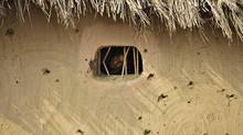 A villager looks out a window of a hut damaged allegedly by gunfire from the Pakistan side of the border at Jora Farm village, in Ranbir Singh Pura region, about 35 kilometres from Jammu, India on Aug. 23. (Channi Anand/AP)