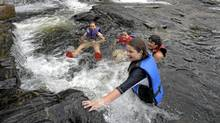 Children play in the waters around Bala Falls, where a proposed run-of-river hydro station has sparked heated opposition from locals. (Fred Lum/The Globe and Mail)