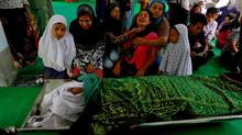 Tin Tin Kyaw (fourth from the left) cries near the body of her husband Soe Min, a 51-year-old man who was killed in a recent riot, at a mosque in Mandalay July 3, 2014. (Soe Zeya Tun/Reuters)