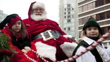 Canucks Place Children's Hospice patient Amadaya Cooke, 8, (L), and her friend Kenzie Oyhenart, 9 ride with Santa Claus during the 7th annual Rogers Santa Claus Parade Dec. 5, 2010. (Brett Beadle for The Globe and Mail/Brett Beadle for The Globe and Mail)