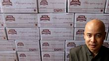 Dang Le Nguyen Vu, general director of Trung Nguyen Coffee, poses in front of boxes of coffee at his factory in Buon Ma Thuot, Vietnam. Mr. Vu estimates that five million people drink his company's coffee every day. (KHAM/REUTERS)