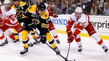 Boston Bruins left wing Milan Lucic battles for the puck with Detroit Red Wings defenseman Danny DeKeyser during the third period in game one of the first round of the 2014 Stanley Cup Playoffs at TD Banknorth Garden in Boston on April 18. (Greg M. Cooper/USA Today Sports)