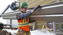 Temporary foreign worker Brian O'Donnell, from Ireland, carries a sheet of cladding while working on the construction of a new police station in Edmonton on April 30, 2012. In Alberta's stretched labour market, some employers have had to turn to overseas labour. (Jason Franson/Jason Franson for The Globe and Mail)