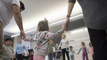 Two and a half year old Aniese Cole (C) holds hands with her mom (R) and another classmate's parent while taking part in the Royal Conservatory's Smart Start program. (Fred Lum/The Globe and Mail)