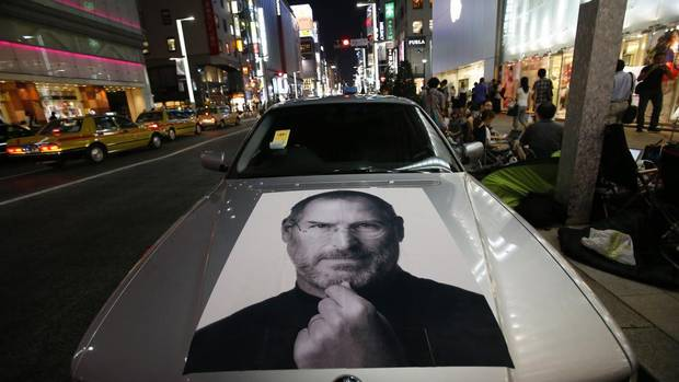 Apple co-founder Steve Jobs is pictured on a BMW near people waiting for the release of the iPhone 5 in front of Apple Store Ginza in Tokyo Sept. 20, 2012. Apple fans queued around city blocks worldwide on Friday to get their hands on the new phone. (Toru Hanai/REUTERS)