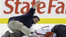"""In this Oct. 24, 2009, file photo, a person signals to the bench after checking on Florida Panthers forward David Booth, who was injured in the second period of an NHL hockey game against the Philadelphia Flyers in Philadelphia. The NHL's new rule banning blindside hits to the head is called """"Rule 48. It easily could be named after victims David Booth and Marc Savard, or offenders Mike Richards and Matt Cooke, who might be the last players to get away with such shots unscathed. For the first time, a lateral or blindside hit on an opponent in which the head is targeted or is the main area of impact will not only be subject to supplemental discipline, but a major penalty and ejection from the game. (AP Photo/Matt Slocum, File) (Matt Slocum)"""