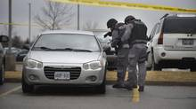 Peel tactical officers approach a car parked in the lot outside the A. Grenville and William Davis Courthouse in Brampton, Ont. on March 28 2014. Charnjit Singh Bassi, 45, of Brampton was killed when he shot at police. (Fred Lum/The Globe and Mail)