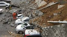 Vehicles crushed by a collapsed wall at a car park in Mito city, Japan. (JIJI PRESS/Jiji Press/AFP/Getty Images)