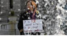 A woman carries a sign during a rally for B.C. teachers in front of the Legislature building in Victoria on Monday. (Chad Hipolito for The Globe and Mail)