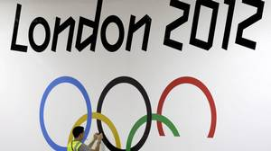 Worker Jack Waller applies the Olympic rings to a wall in the ExCel Center in preparation for the start of the 2012 Summer Olympics, Thursday, July 26, 2012, in London.