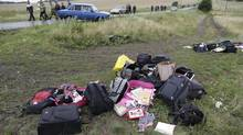 <137>Rescue <137>Workers walk past MH17 passengers' luggage near the village of Hrabove, Ukraine, on Friday. (Dmitry Lovetsky/AP)