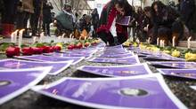 Photos and roses are placed in a memorial to missing women in Vancouver on Dec. 17, 2012, before the report from the Missing Women Commission of Inquiry is released. (John Lehmann/The Globe and Mail)
