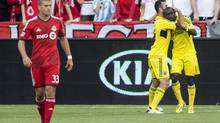 Columbus Crew's Dominic Oduro, right, celebrates with Justin Meram after scoring as Toronto FC's Ryan Richter, left, looks on during first half MLS action in Toronto on Saturday, May 18, 2013. (Chris Young/THE CANADIAN PRESS)
